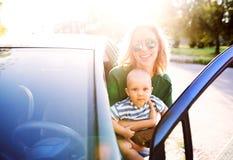 有她的进入汽车的小男婴的年轻母亲 免版税库存图片