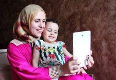 有她的采取selfie的女婴的愉快的阿拉伯回教母亲 免版税库存图片