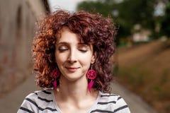 有她的闭上的眼睛的微笑的红头发人妇女 库存照片