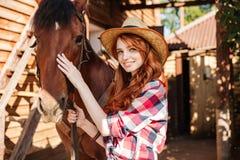 有她的马的愉快的妇女女牛仔在村庄 免版税库存照片