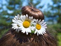 有她的头发的女孩在小圆面包和春黄菊 免版税库存照片