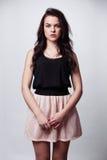 有她的头发的年轻深色的女孩在一条相当桃红色裙子看i 库存图片
