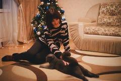 有她的戴圣诞老人帽子的猫的妇女在圣诞树附近 免版税库存图片