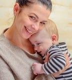 有她的婴孩的快乐的爱恋的年轻母亲 库存照片