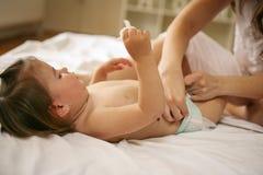 有她的婴孩的母亲在家 母亲改变的尿布她小 库存照片