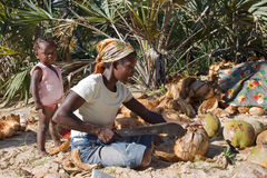 有她的婴孩的母亲打开与大砍刀的一个椰子 免版税库存照片
