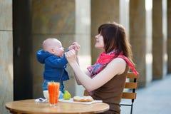 有她的婴孩的美丽的年轻母亲咖啡馆的 库存图片