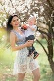 有她的婴孩的年轻母亲在步行的胳膊的在开花的庭院里 库存照片