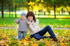 有她的婴孩的年轻母亲在秋天 图库摄影