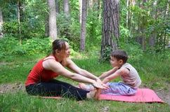 有她的9岁的健身母亲儿子 有做早晨的孩子的体育妈妈在公园解决 妈咪和孩子做 免版税库存图片