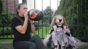 有她的Daugher的母亲吹气球室外 由于今天是万圣夜,他们获得很多乐趣 影视素材