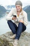 有她的Smartphone的新白肤金发的妇女在现有量 免版税图库摄影
