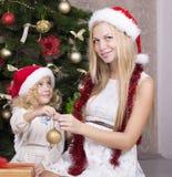 有她美丽的母亲的逗人喜爱的小女孩圣诞老人的帽子的 免版税库存图片
