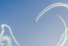 有她色的飞机的特技飞行员训练在蓝天的 库存图片