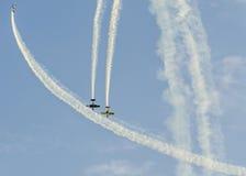 有她色的飞机的特技飞行员训练在蓝天的 免版税库存图片