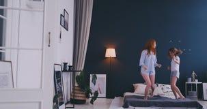 有她获得乐趣学会舞蹈现代样式的爱恋的母亲的滑稽的女孩一起观看在电视的跳舞的展示和 影视素材