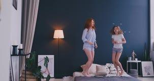有她获得乐趣学会舞蹈现代样式的爱恋的母亲的滑稽的女孩一起观看在电视的跳舞的展示和 股票录像