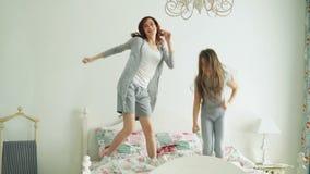 有她获得乐趣学会舞蹈现代样式的爱恋的母亲的滑稽的小女孩一起观看在电视的跳舞展示和 股票视频