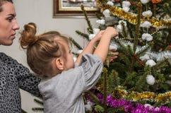 有她迷人的女儿的年轻美丽的母亲装饰玩具和诗歌选保存家庭价值观和传统的圣诞树 免版税库存照片