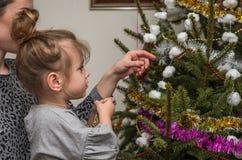 有她迷人的女儿的年轻美丽的母亲装饰玩具和诗歌选保存家庭价值观和传统的圣诞树 图库摄影