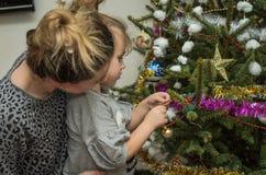 有她迷人的女儿的年轻美丽的母亲装饰玩具和诗歌选保存家庭价值观和传统的圣诞树 库存照片