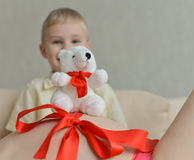 有她逗人喜爱的小男孩的怀孕的母亲沙发的 图库摄影