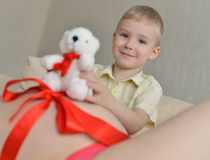 有她逗人喜爱的小男孩的怀孕的母亲沙发的 免版税库存照片
