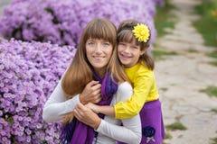 有她逗人喜爱的微笑的女儿女孩的美丽的白肤金发的母亲妈妈穿五颜六色的衣裳一起享受时间的接近紫色flo 库存照片