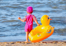 有她逗人喜爱的游泳圆环的小女孩 免版税库存照片
