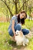 有她逗人喜爱的狗的微笑的妇女 免版税库存图片