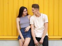 有她逗人喜爱的男朋友的一个attracive女孩饱和的黄色背景的 关系和爱概念 库存图片