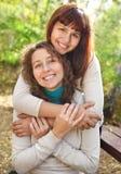 有她青少年的女儿的新微笑的妇女 库存照片