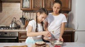 有她青少年的女儿的母亲一起烹调与奶油的手工制造巧克力蛋糕 股票视频