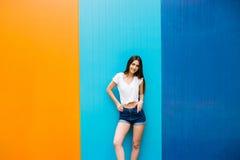 有好的身体的女孩反对颜色墙壁背景 免版税图库摄影