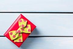 有好的蝴蝶的红色礼物盒在蓝色木背景 文本的空位 免版税库存图片