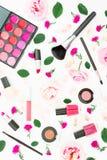 有妇女化妆用品、辅助部件和桃红色玫瑰的时髦的书桌在白色背景 平的位置,顶视图 秀丽背景 图库摄影