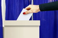 有妇女手决定票的投票箱 免版税库存图片