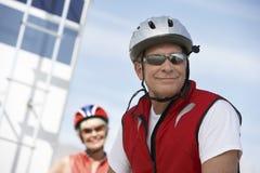 有妇女的微笑的男性骑自行车者在背景中 免版税库存照片