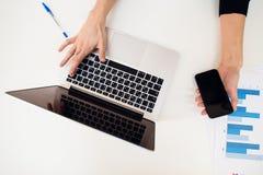 有妇女的手膝上型计算机和在白色桌上的纸图表 图库摄影