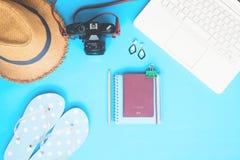 有妇女辅助部件、照相机和护照的白色便携式计算机在蓝色颜色背景,夏天旅行 库存图片