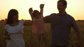 有妈妈和爸爸旅行的愉快的女儿在成熟麦子的领域,儿童笑附近 r 婴孩与 股票录像