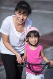 有妈妈指南的亚洲中国小女孩骑马自行车 免版税库存照片