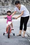 有妈妈指南的亚洲中国小女孩骑马自行车 免版税库存图片