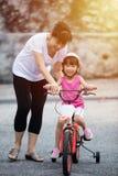 有妈妈指南的亚洲中国小女孩骑马自行车 库存图片