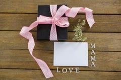 有妈妈爱文本的礼物盒在木板条 库存图片