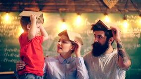 有妈妈的一个男孩和爸爸获得乐趣在与书的学校课程在他们的头 概念了解 回到学校 影视素材