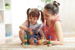 有妈妈的儿童女孩在家使用与教育玩具在托儿所 免版税库存照片