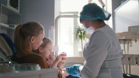 有妈妈的小女孩在牙医屋子里-医生审查女孩` s牙 股票录像