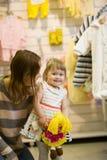 有妈妈的小女婴在衣裳商店 免版税库存照片