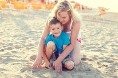 有妈妈的小男孩海滩的 免版税库存照片